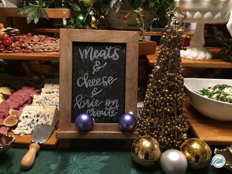 Holiday appetizer table with closeup of cheese and charcuterie assortment with fruit, grapes, nuts, and holiday decor