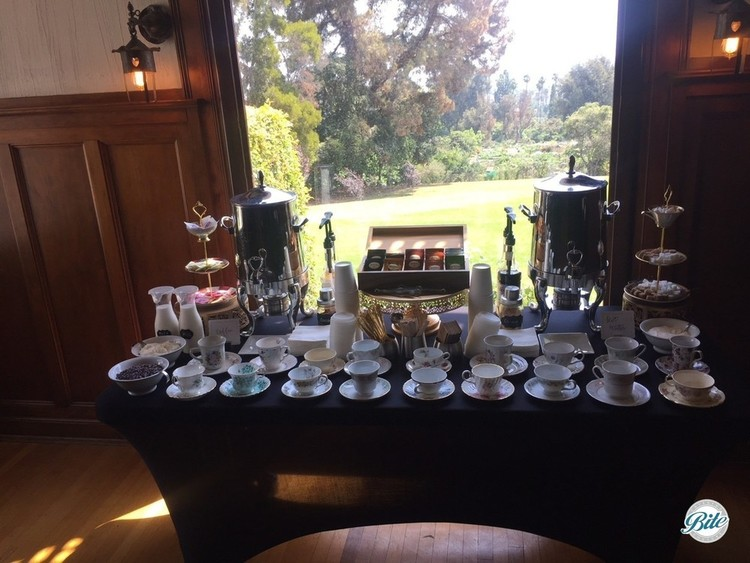 Tea setup with assorted vintage teacups overlooking lawn at Wattles Mansion