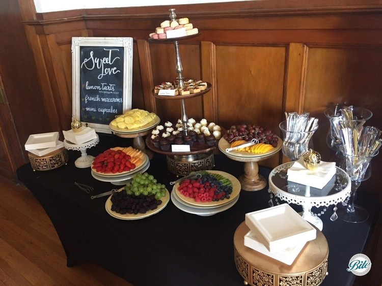 Dessert table with assorted fresh fruit, lemon tarts, french macarons, and mini cupcakes