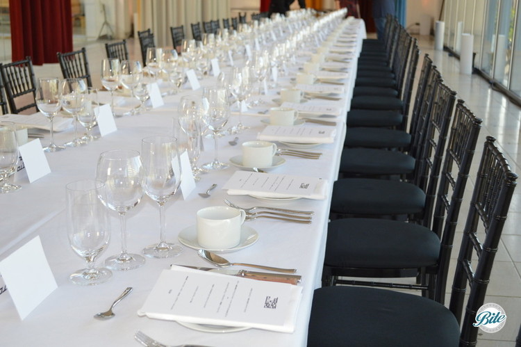 Long table set for plated dinner. Individual name cards and menus provided.