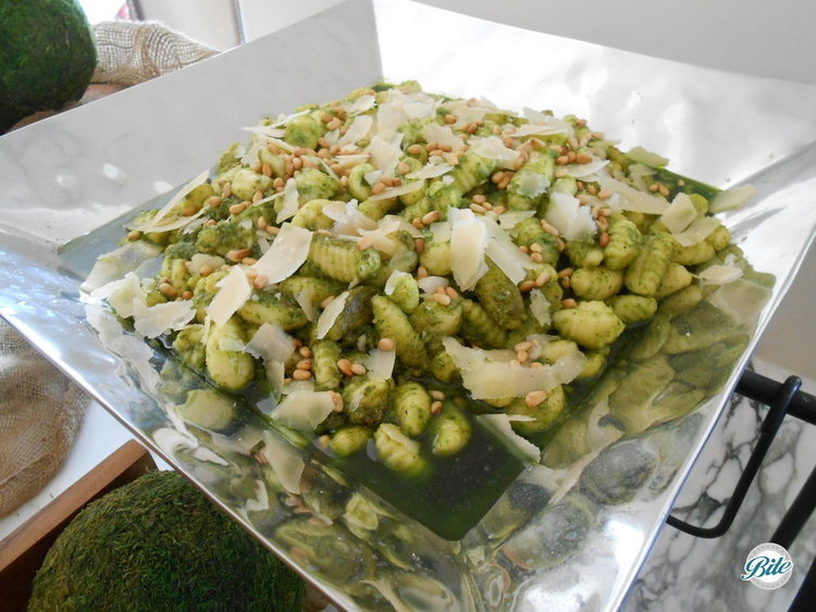 Side of gnocchi on a buffet. Sauteed in fresh arugula pesto and served with shaved parmesan and pine nuts