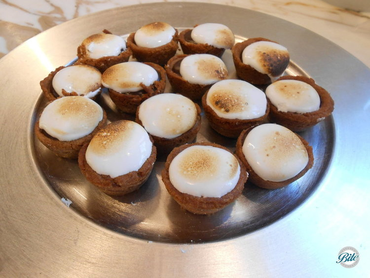 Mini s'mores bites with graham cracker-chocolate chip cookie crust, chocolate ganache,  dulche de leche and toasted marshmallow cream