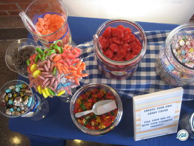 Candy buffet with: jelly beans, lollipops, gum drops, red vines, gummy bears, and salt water taffy on picnic display with blue and white linens