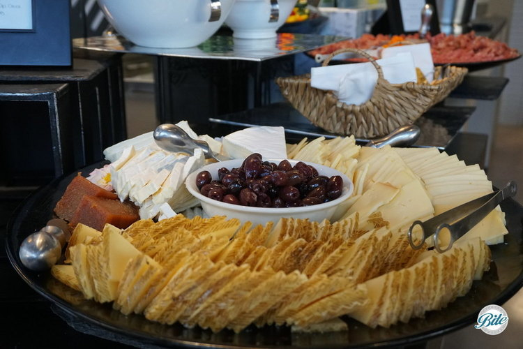 Closeup of three cheese assortment, served with with preserves and olives. On cheese and charcuterie display