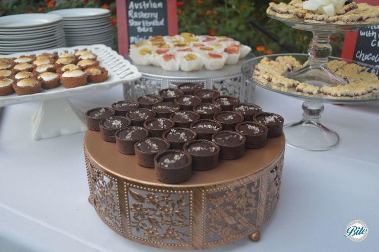Chocolate Salted Caramel Tartlets. On bronze riser on dessert display.