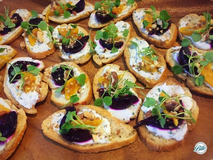 Crostini with beets, herb goat cheese, microgreens, and hazelnuts