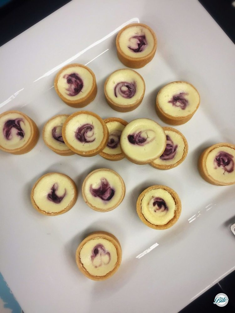 Cheescake Tarts with Mixed Berry. On dessert display.