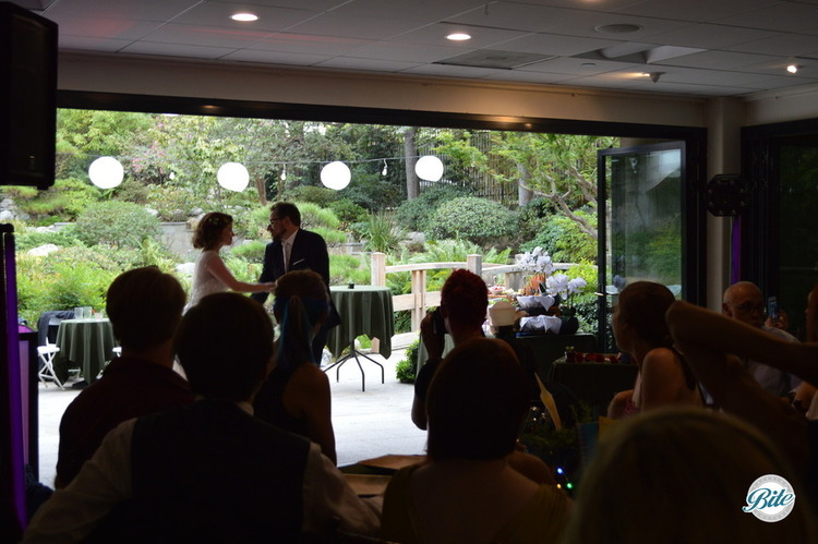 Bride and groom dancing in the open doors in front of the beautiful gardens at JACCC