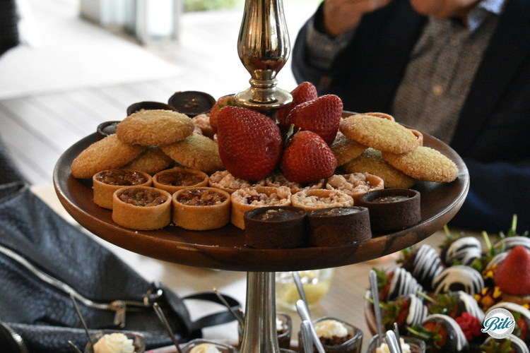 Dessert assortment on tray above the dessert shots and chocolate covered strawberries.  Assortment of cookies, fruit, chocolate tarts, caramel pecan tarts, berry tarts, and more!