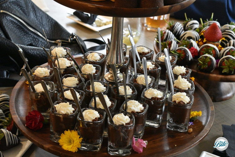 Individual chocolate dessert shots in shot glasses with mini spoons.
