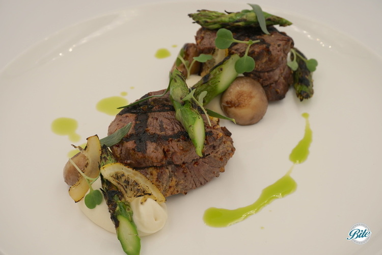 Grilled duo of beef medallions. Wet aged with mustard and tarragon, flambéed mushrooms, pickled pearl onions, chive oil, and caramelized lemon. served with celeriac puree and charred asparagus