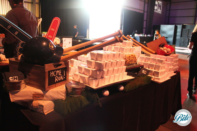 Asian noodle take out boxes on stationary bite display for sports themed event. The display features foam fingers, balls, stacked crates, AstroTurf for flair.