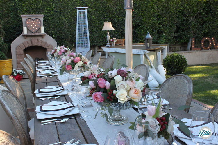 A beautiful evening dinner set in the garden. Lovely florals decorate a wooden table.