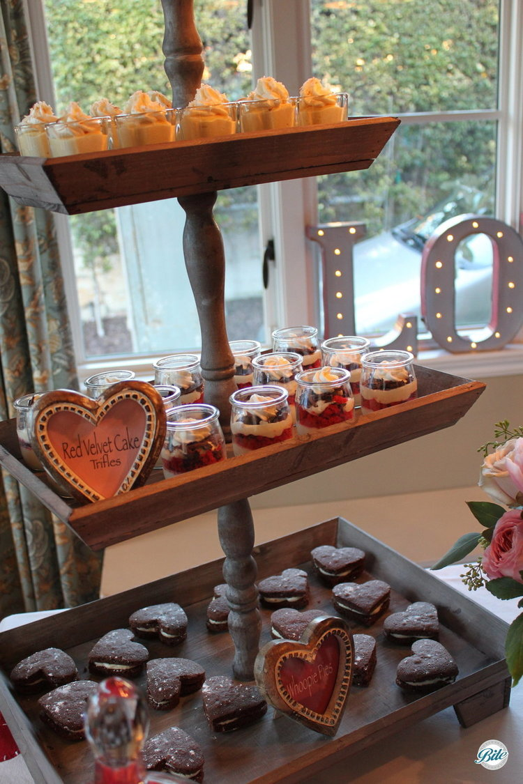 A tiered dessert display filled with sweet things. Red Velvet cake trifles, heart-shaped whoopie pies, and passionfruit mousse