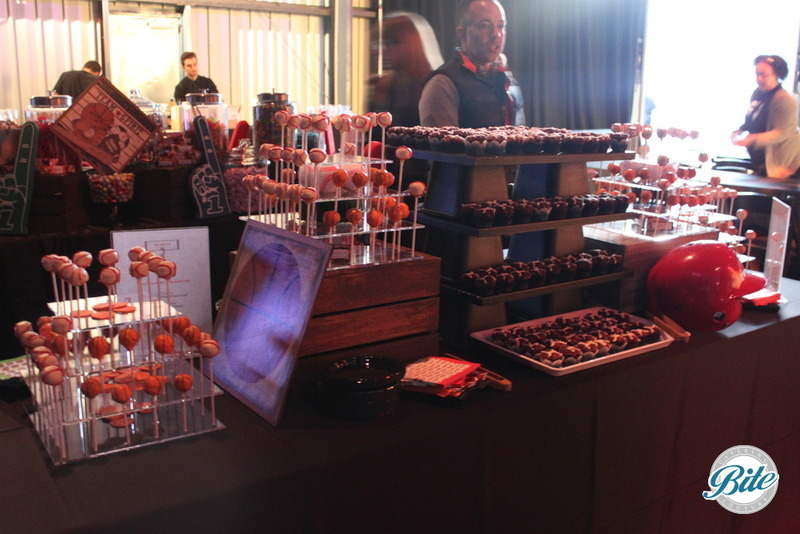 Dessert display with basketball and baseball caked pops an football cupcakes on tiered displays with foam fingers, and helmets for corporate event