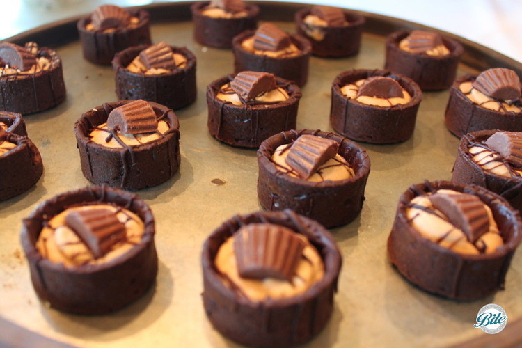 Mini chocolate peanut butter pies on golden tray.