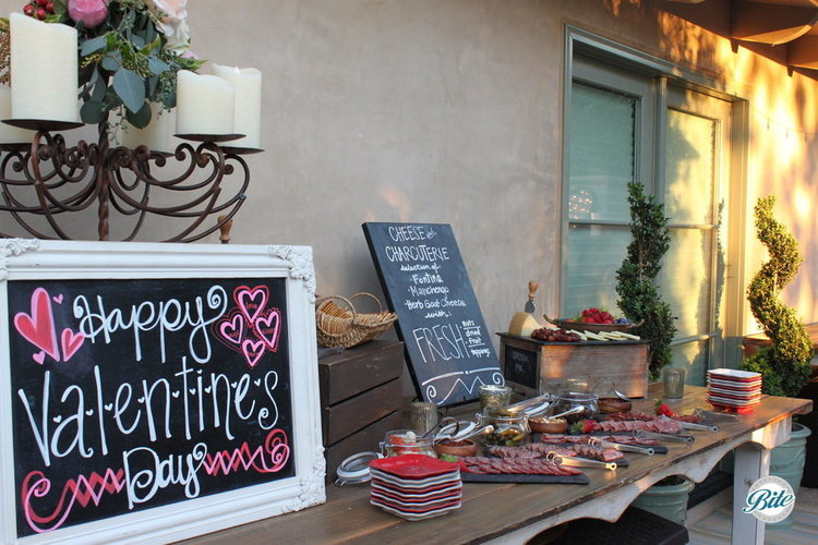 Valentine's Day signage decorates the cheese and charcuterie table