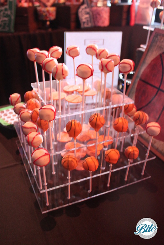 Cheesecake flavored, ball themed cake pops on modern acrylic display for presentation.