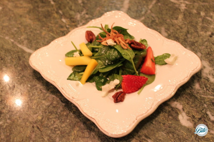 Baby spinach salad with fresh mango, strawberry, goats cheese mousse, candied pecans, frizzled shallot garnish and champagne vinaigrette