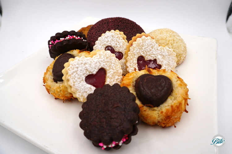An assortment of cookies for Valentine's Day. Chocolate crinkles. Chocolate sandwich cookies with buttercream and sprinkle garnish. Heart-shaped linzer cookies with jam. Thumbprint cookies with chocolate heart centers