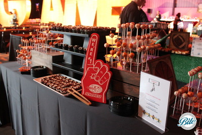 Ball cake pops, brownie football cupcakes and foam fingers on black, wood and AstroTurf display with over-sized marquee lighting for private party.