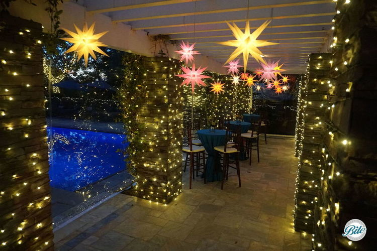 A clear tent creates a beautifully lit up covered space (with twinkling lights and stars) next to the pool on a crisp winter evening.  A terrific waterfront view from the nearby hightops!