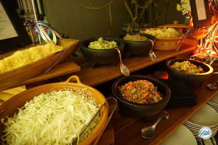 Toppings on the Taco Bar. Including shredded cheese, shredded cabbage, pico de gallo, guacamole, salsa, mango salsa.