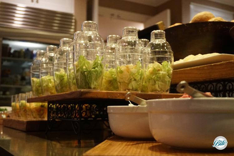 Shaker salad bar with closeup of caeser salads on a riser