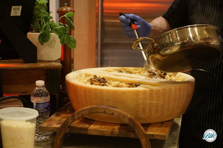 Chef preparing a fresh pasta station served in a parmesan wheel. Spooning hot pasta into the wheel to melt the parmesan into the dish.