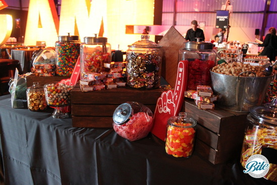 Game themed candy buffet with wooden crates and candy jars filled with peanuts, peach rings, gumballs, cracker jack, chocolate and gummy bears.