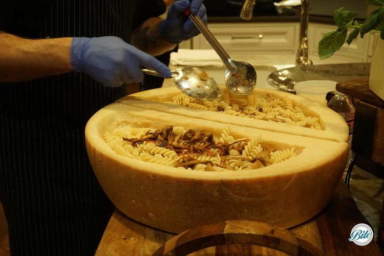 Chef preparing a wild mushroom pasta to serve in a hollowed parmesan wheel.