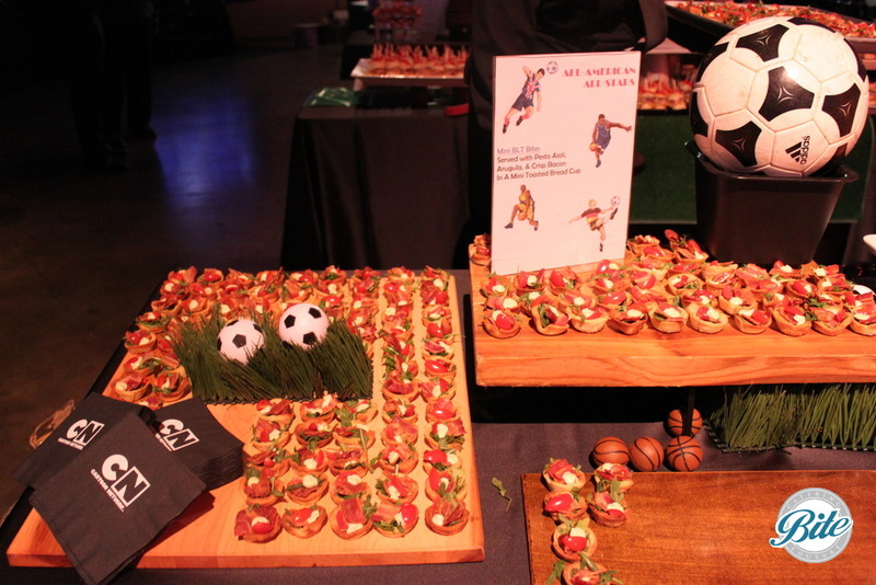BLT canape with pesto aoli in toasted bread cup on soccer themed display with grass, soccer balls and wooden trays