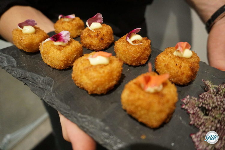 mac'n cheese bites with truffle aioli and edible flower garnish