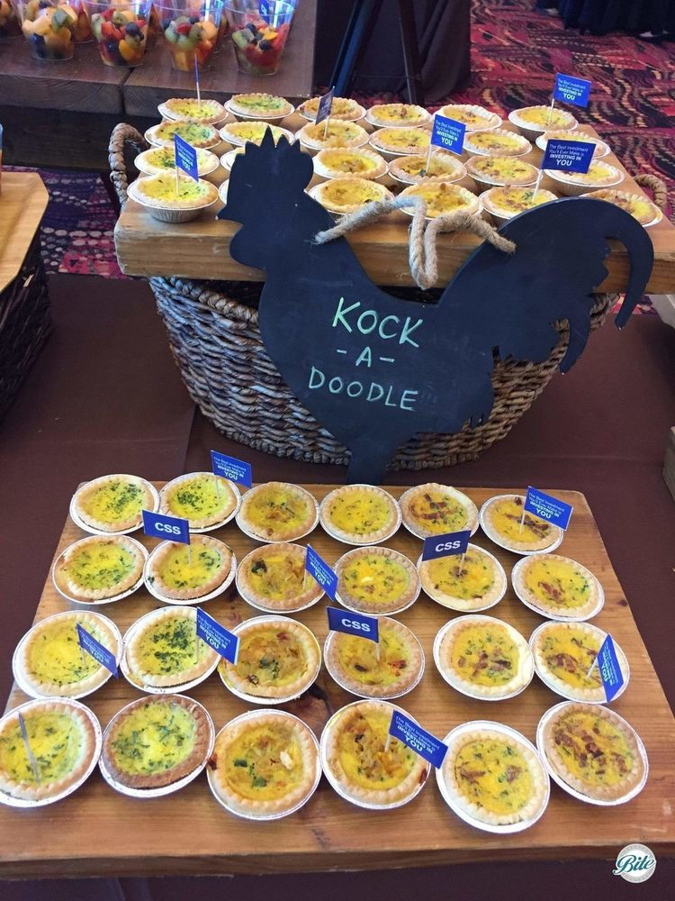 Assorted Quiche flavors including Seasonal Vegetable, Cowboy Quiche, Quiche au fromage. On display with chalkboard rooster.