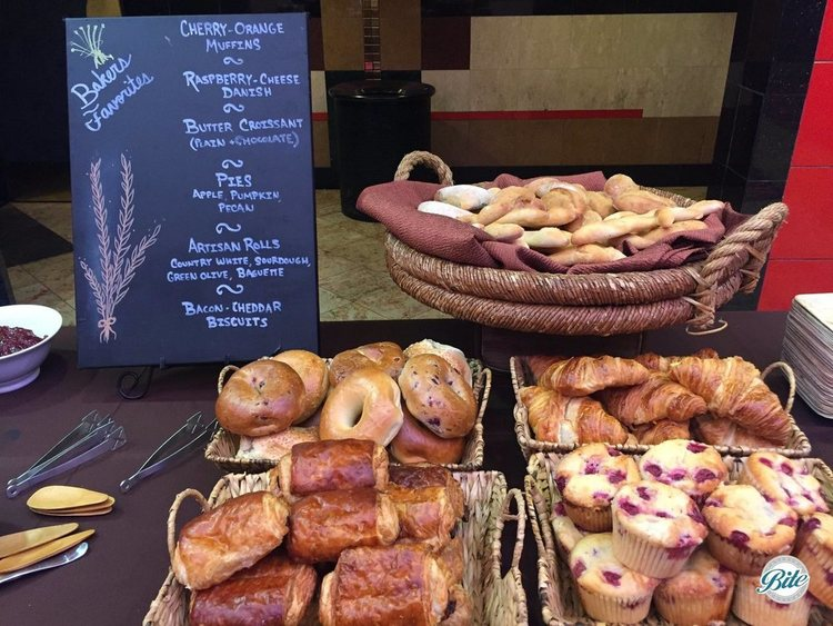 Assorted Breakfast Breads in baskets. Cherry-orange muffins, butter croissants with assorted spreads, raspberry-cheese danish, bagels, artisan rolls