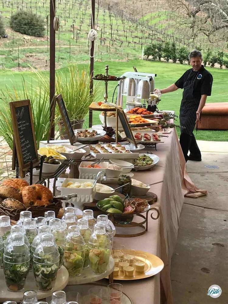 Chef finishing setup of a beautiful buffet looking out over a lush vineyard