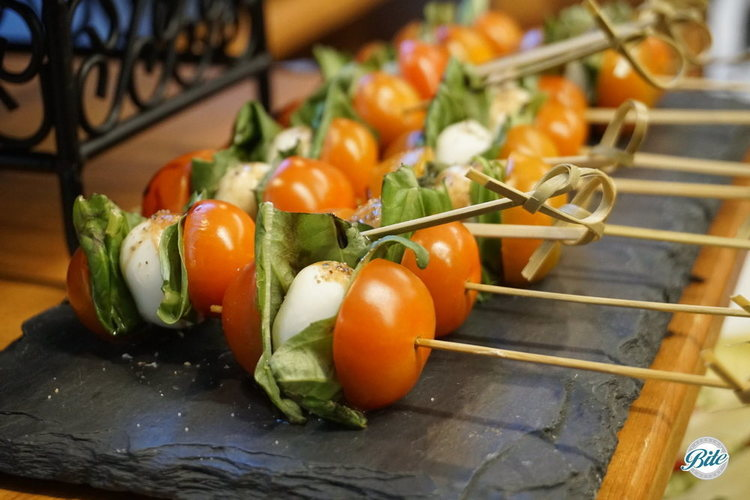 Caprese skewers with ciliegine mozzarella, cherry tomato, basil. Drizzled with olive oil and balsamic reduction.