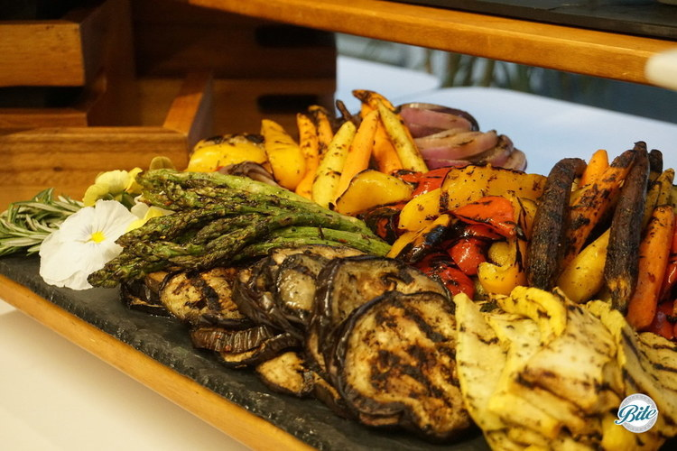Seasonal grilled vegetables on buffet. Grilled rainbow carrots, bell peppers, asparagus, squash, onions, and more.