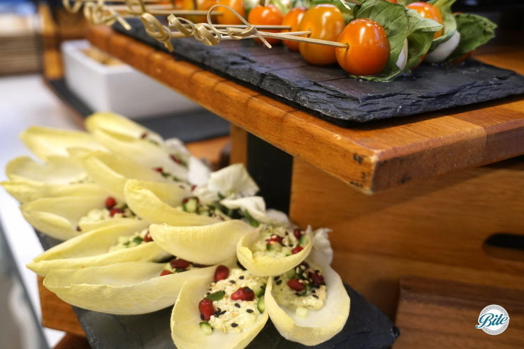 Endive canapes filled with edamame hummus, cucumber, pomegranate jewels, and toasted sesame seeds.