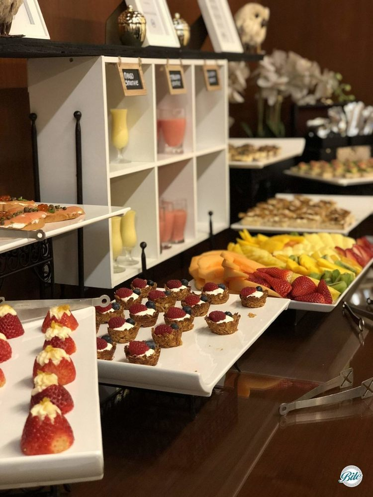 A stationary breakfast display with strawberry canape, bagel and lox canape, smoothie shots, and tartines