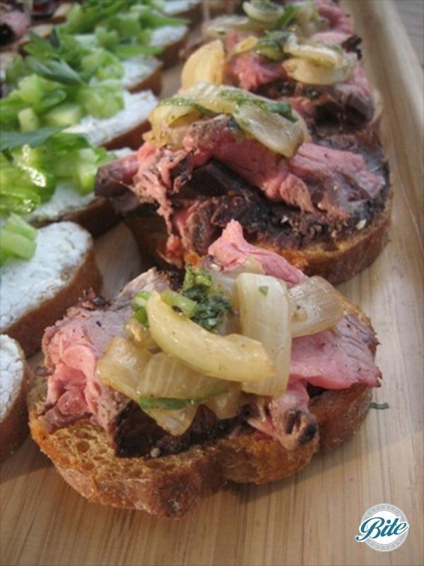Flank steak crostini, with chimichurri, grilled vidalia relish, and sriracha aioli