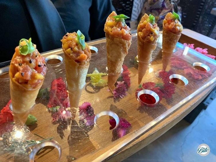 Ahi tuna tartare presented in a vertical cone by server. Served with sriracha vinaigrette, sweet mango and lime-avocado cream.