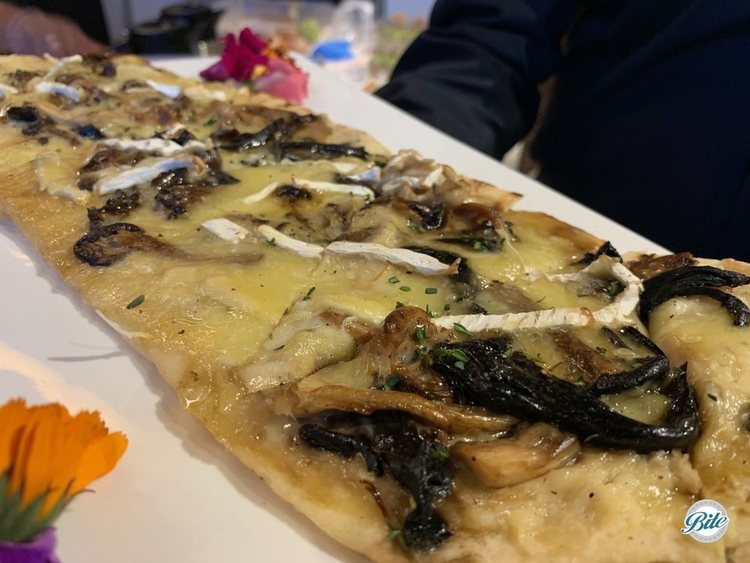 Flatbread topped with yummy raclette, wild mushrooms, brie, shallots, herbs, and truffle oil.