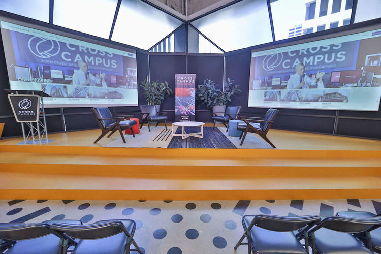 Stage set for a roundtable and highlighting the two large, high definition presentation screens