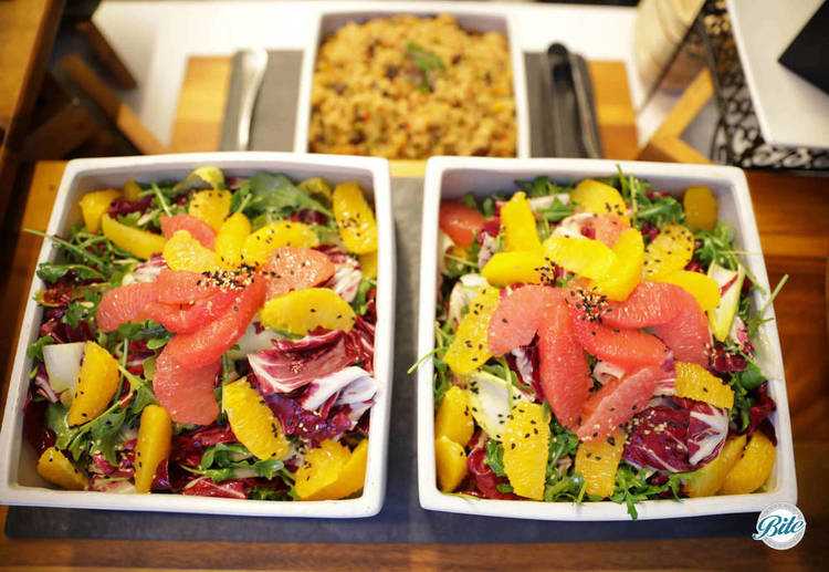 Citrus salads in square bowls on display.  Seen from above.