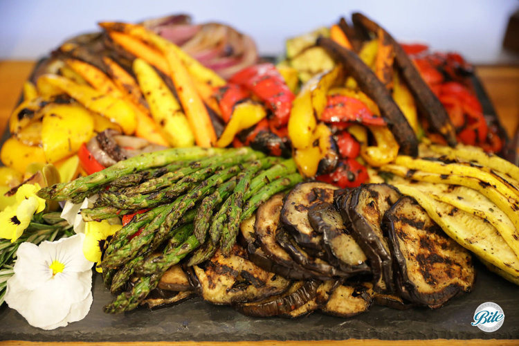 Roasted vegetables including squash, asparagus, eggplant, carrots, peppers. On a slate tray garnished with edible flowers and herbs.
