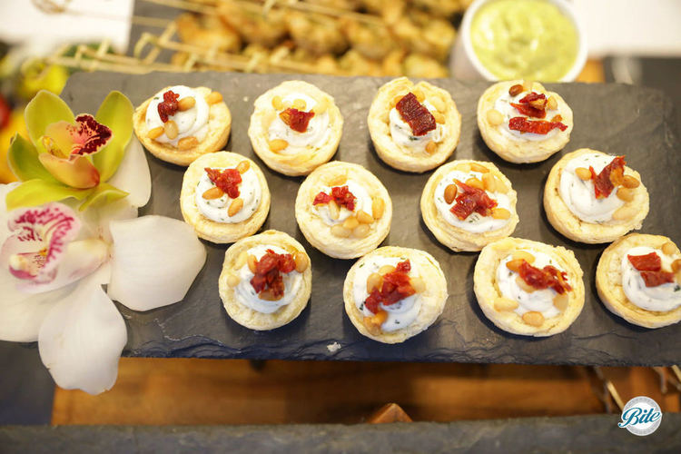 Puff pastry cups with herb goat cheese, sun-dried tomatoes and toasted pine nuts. Displayed on slate tray with metal risers. Viewed from above.