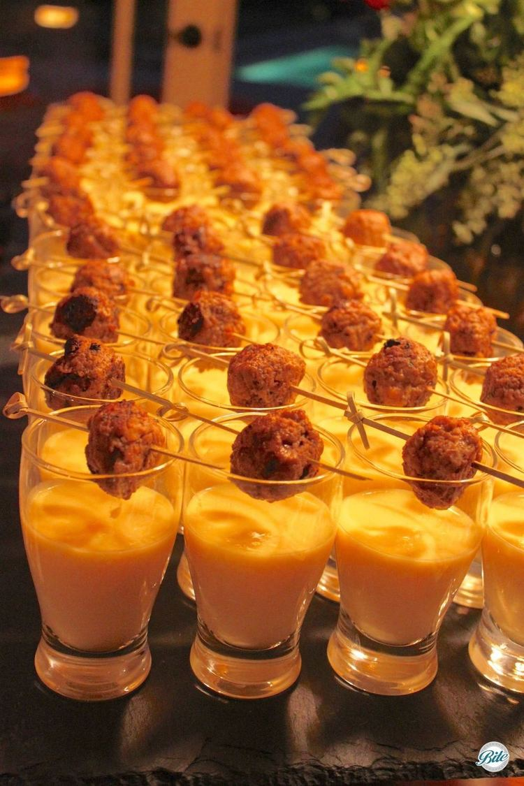 Spiced lamb meatballs on skewers placed above a mango lassi shot (in mini glass)
