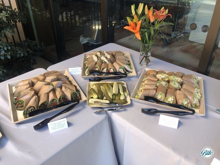 Assortment of Wraps including California Veggie Lovers, Applewood Smoked Turkey and Havarti, and Southwest with Chicken. Served with pickles and presented on reusable wood trays.