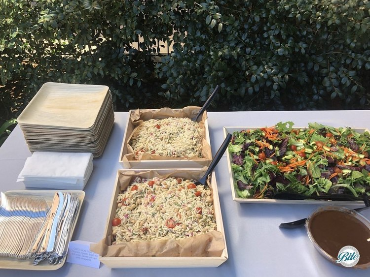 Salads served in wood trays as part of Boardroom. Orzo salad and mixed greens salad.